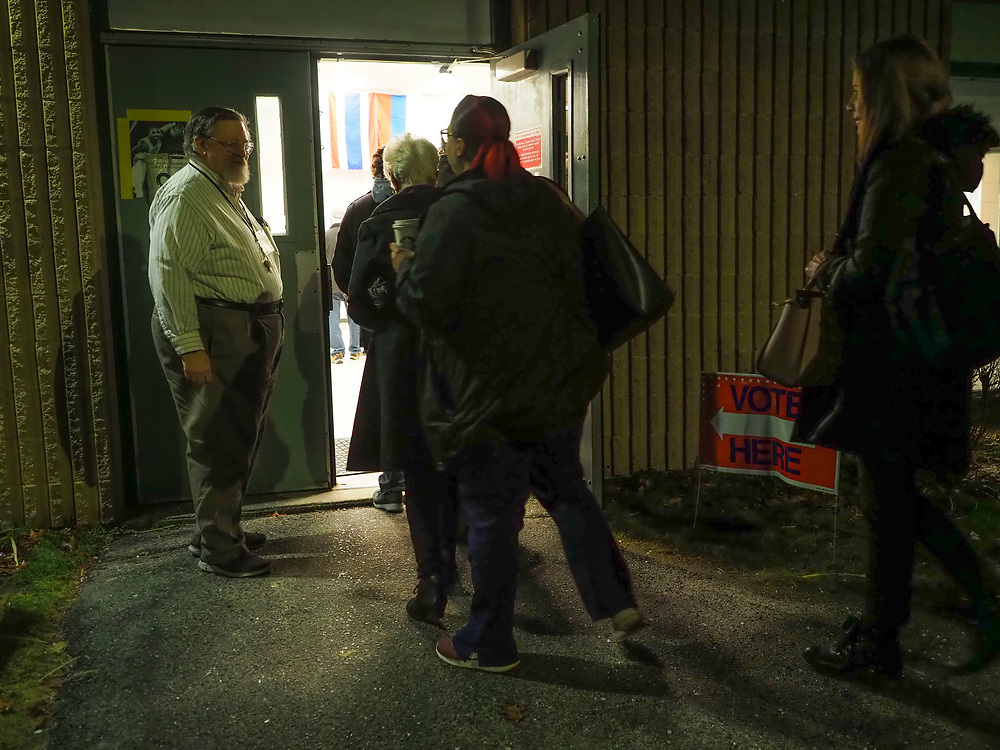 Voting moderator John B. Lisle opens the door to let in the more than three dozen voters who waited in line prior to the Nashua NH polling site's 6am opening. Nashua is one of a handful on New Hampshire towns that opens polls early and closes late.