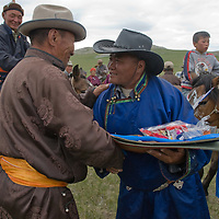 A clan elder presents prizes after a traditional naadam festival on a remote pass near Muren, Mongolia.