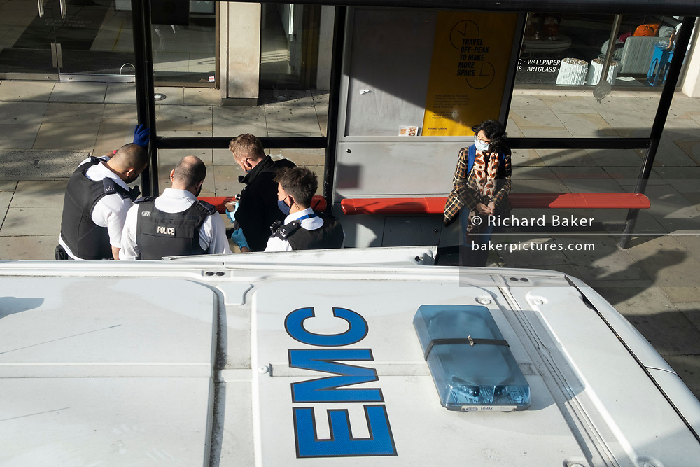 As a bus passenger awaits the next service, four Met Police officers attend to an unseen elderly person at a bus stop in Chelsea, during the second wave of the Coronavirus pandemic, on 20th October 2020, in London, England.