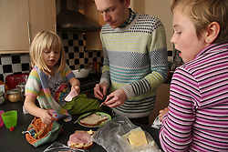 Father and daughters making a sandwich