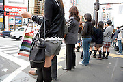 various women standing waiting to cross the street Tokyo Japan