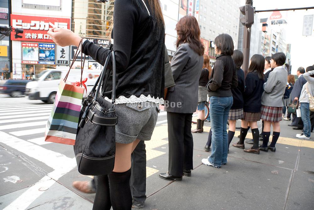 various women standing waiting to cross the street Tokyo Japan