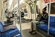 People wearing face masks on a London Underground train on 27th August in London, United Kingdom. Face covering advice by TfL Transport for London at this time is the following: Face coverings must be worn for the full duration of journeys on the TfL network, including inside stations.