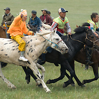 Young, costumed bareback riders approach the finish line of a 20km race at a traditional naadam festival on a remote pass near Muren, Mongolia.