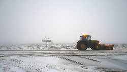 © Licensed to London News Pictures. 27/01/2014 North York Moors, England A tractor snow plough makes its way through early morning fog as it continues to keep the main road across the North York Moors clear following another night of snow. Photo credit : Ian Forsyth/LNP