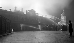The inferno gives a strange floodlight effect as the fire continues at the Union Cold Storage Company at Smithfield Market, London.