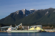 """North Vancouver industrial area with a view of Crown and Grouse Mountains from Vancouver.  The ship anchored at the North Vancouver Sulphur Works is the """"La Bamba"""" (Marshall Islands) loading up with sulphur for export.  Photographed from the Vancouver Trade and Convention Center in Vancouver, British Columbia, Canada"""