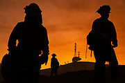 HEALDSBURG, CA - OCTOBER 26: Members of an inmate firefighting crew are silhouetted against a hillside with a track of PG&E lines during firefighting operations to battle the Kincade Fire in Healdsburg, California on October 26, 2019.