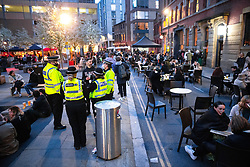 © Licensed to London News Pictures. 12/04/2021. Manchester, UK. Police on duty in Cutting Room Square in Ancoats . People on a night out in Manchester City Centre as government restrictions to control the spread of Coronavirus are eased across the UK. Pubs, restaurants, hairdressers, gyms and non essential retailers are now permitted to serve customers within restrictions. Photo credit: Joel Goodman/LNP