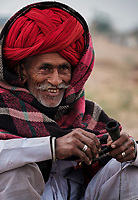 PUSHKAR, INDIA - CIRCA NOVEMBER 2016: Camel herder smoking early morning in the Pushkar Camel Fair grounds. It is one of the world's largest camel fairs. Apart from the buying and selling of livestock, it has become an important tourist attraction.