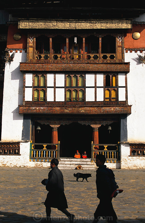 Gangte Goemba (Monastery) in Phobjikha Valley, Bhutan. Young Buddhist monks practice reading holy scripts aloud in an entryway. The monastery dates back to the 1600's and includes one of the largest prayer halls in the tiny Himalayan country and a meditation center for monks. The government financed the building of a Buddhist college here in the 1980's. From coverage of revisit to Material World Project family in Bhutan, 2001.