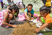 13 MAY 2013 - BANGKOK, THAILAND:   A family sifts through the sand they took from the Royal Ploughing Ceremony looking for blessed rice seeds sown by court Brahmins in Bangkok. After the ceremony, thousands of Thais, mostly family formers, rush onto the ploughed ground to gather up the blessed rice seeds sown by the Brahmin priests. The Royal Plowing Ceremony is held Thailand to mark the traditional beginning of the rice-growing season. The date is usually in May, but is determined by court astrologers and varies year to year. During the ceremony, two sacred oxen are hitched to a wooden plough and plough a small field on Sanam Luang (across from the Grand Palace), while rice seed is sown by court Brahmins. After the ploughing, the oxen are offered plates of food, including rice, corn, green beans, sesame, fresh-cut grass, water and rice whisky. Depending on what the oxen eat, court astrologers and Brahmins make a prediction on whether the coming growing season will be bountiful or not. The ceremony is rooted in Brahman belief, and is held to ensure a good harvest. A similar ceremony is held in Cambodia.  PHOTO BY JACK KURTZ