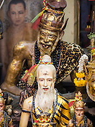 "25 MAY 2015 - BANGKOK, THAILAND: Statues of deities with a picture of Bhumibol Adulyadej, the King of Thailand, in the background, are a part of the shrine in Ajarn Neng Onnut's Sak Yant tattoo parlor. Sak Yant (Thai for ""tattoos of mystical drawings"" sak=tattoo, yantra=mystical drawing) tattoos are popular throughout Thailand, Cambodia, Laos and Myanmar. The tattoos are believed to impart magical powers to the people who have them. People get the tattoos to address specific needs. For example, a business person would get a tattoo to make his business successful, and a soldier would get a tattoo to help him in battle. The tattoos are blessed by monks or people who have magical powers. Ajarn Neng, a revered tattoo master in Bangkok, uses stainless steel needles to tattoo, other tattoo masters use bamboo needles. The tattoos are growing in popularity with tourists, but Thai religious leaders try to discourage tattoo masters from giving tourists tattoos for ornamental reasons.       PHOTO BY JACK KURTZ"