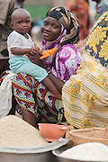 A woman holding her son sells rice at a roadside market in Bouake, Cote d'Ivoire on Sunday July 14, 2013.