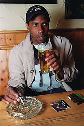 Young man sitting at table in pub drinking pint of beer and smoking cigarette,