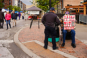15 MAY 2021 - DES MOINES, IOWA: A street preacher talks to a Des Moines police officer at the Farmers Market Saturday. The Des Moines Farmers Market is the largest weekly Farmers Market in Iowa. The market was largely cancelled in 2020 because of COVID-19 pandemic, but reopened in a limited way in 2021. In order to comply with Coronavirus safety guidelines, traffic is one way past the stands and people are required to wear face masks. Traditionally about 25,000 people attended the Saturday morning market, and about 40,000 people attended market on the opening day, the first Saturday in May. This year there will be about 115 vendors, 75% the normal number of vendors. As the CDC rolls back Coronavirus guidelines, the market is expanding. The market will expand Memorial Day weekend to include prepared food stands and children's activities.          PHOTO BY JACK KURTZ