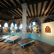 An exhibit hall in Old St. John's Hospital in Bruges, Belgium. In the foreground are tombstone slabs rescued from building renovations. Old St. John's Hospital is one of Europe's oldest surviving hospital buildings that dates to the 11th century. It originally treated sick pilgrims and travelers. A monastery and convent was later added. It is now a museum.