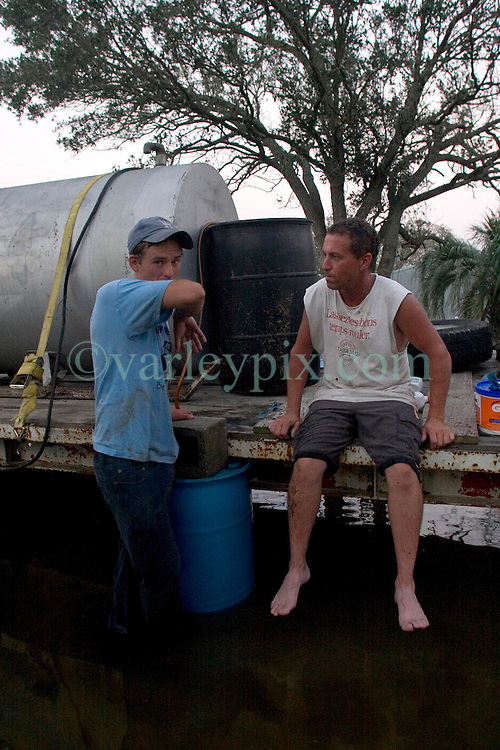 25 Sept, 2005. Carlyss, Louisiana. Hurricane Rita aftermath. <br /> Friends and relatives help neighbour Harold Herman (white t/rt) to syphon diesel fuel from a 500 gallon drum for use in his generator. Locals helped each other through the aftermath of the storm.<br /> Photo; ©Charlie Varley/varleypix.com