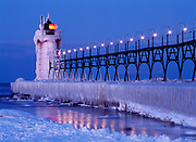 Ice-covered South Haven Pier Lighthouse illuminated at dawn, mouth of the Black River into Lake Michigan, South Haven, Michigan.
