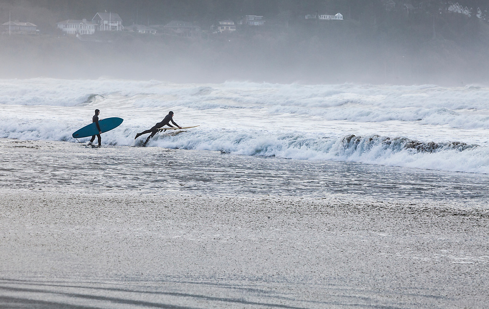 Two young men headed out into the suf with surfboards. Pacific coast, Seaside, Oregon, USA.