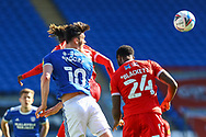 Cardiff City's Kieffer Moore (10) competes for a high ball with  Nottingham Forest's Alex Mighten (17) while Tyler Blackett (24) looks on during the EFL Sky Bet Championship match between Cardiff City and Nottingham Forest at the Cardiff City Stadium, Cardiff, Wales on 2 April 2021.