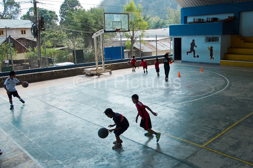 Two boys playing basketball in a covered court, in San Pedro La Laguna, Guatemala.