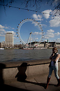 Woman takes a cell phone call beside the river opposite the London Eye.