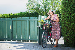 Senior woman entering garden gate with bicycle and vegetable, Bavaria, Germany