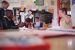 Primary school children sitting around desks in classroom during art and craft lesson,