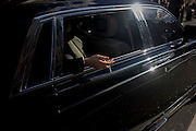 A welathy man's hand hangs outside his shiny black limousine, holding a cigarette