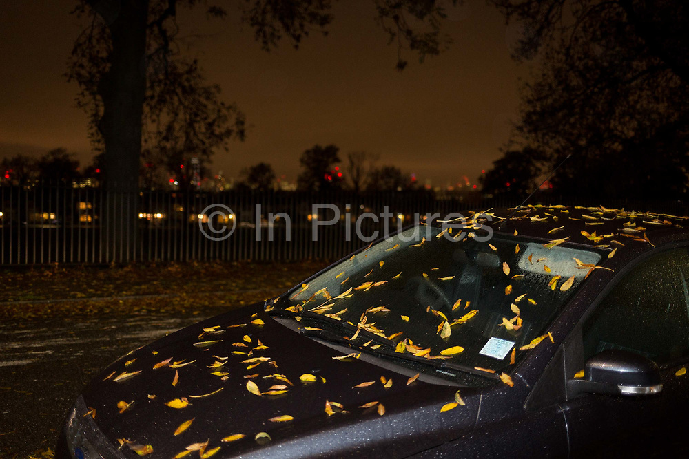 Autumnal leaves on the roof and bonnet hood of a parked car in the evening in a south London street, on 26th October 2017, in London, England.