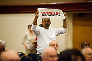 BIRMINGHAM, AL –SEPTEMBER 16, 2012: AN Undocumented Hispanic protestor is escorted out of a briefing on the civil rights effects of state immigration law held by the U.S. Commission on Civil Rights in Birmingham, Alabama on August 17, 2012. The protestor is one of several undocumented Latinos traveling across the country on the Undocubus.