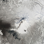 """Five Volcanoes Erupting at Once<br /> <br /> Remote. Cold. Rugged. Those three adjectives capture the essence of Russia's Kamchatka Peninsula. Another word—perhaps more applicable than anywhere else on Earth—is """"fiery.""""<br /> Of the roughly 1,550 volcanoes that have erupted in the recent geologic past, 113 are found on Kamchatka. Forty Kamchatkan volcanoes are """"active,"""" either erupting now or capable of erupting on short notice. The Operational Land Imager (OLI) on Landsat 8 captured activity at five of them during a single satellite pass on April 14, 2014.<br /> From geographic north to south (and top to bottom on this page), the volcanoes are Shiveluch, Klyuchevskaya, Bezymianny, Kizimen, and Karymsky. The tallest of the group is Klyuchevskaya, a stratovolcano with a steep, symmetrical cone that reaches 4,750 meters (15,580 feet) above sea level. The most active is Karymsky, a 1,536-meter (5,039-foot) peak that has erupted regularly since 1996.<br /> Plate tectonics is responsible for the many volcanoes on Kamchatka Peninsula. The Pacific Plate is slowly colliding with and sliding beneath the Okhotsk Plate. As rock from the Pacific Plate descends and encounters higher pressures and temperatures, it melts into magma. Over time, magma accumulates and migrates up toward the surface, causing volcanic eruptions.<br /> Long before the discovery of plate tectonics, Kamchatka's many volcanoes and eruptions were woven into a rich tapestry of myths and creation stories. According to Koryak folklore, the raven-like deity Kutkh created Kamchatka by dropping a giant feather on the Pacific Ocean. Each of the first generation of men became one of Kamchatka's mountains at death; many of these mountains became volcanic because the men's hearts burned so passionately for a beautiful woman that Kutkh had also created near the beginning of time.<br /> Photo Shows shiveluch<br /> ©Earth Observatory/Exclusivepix"""