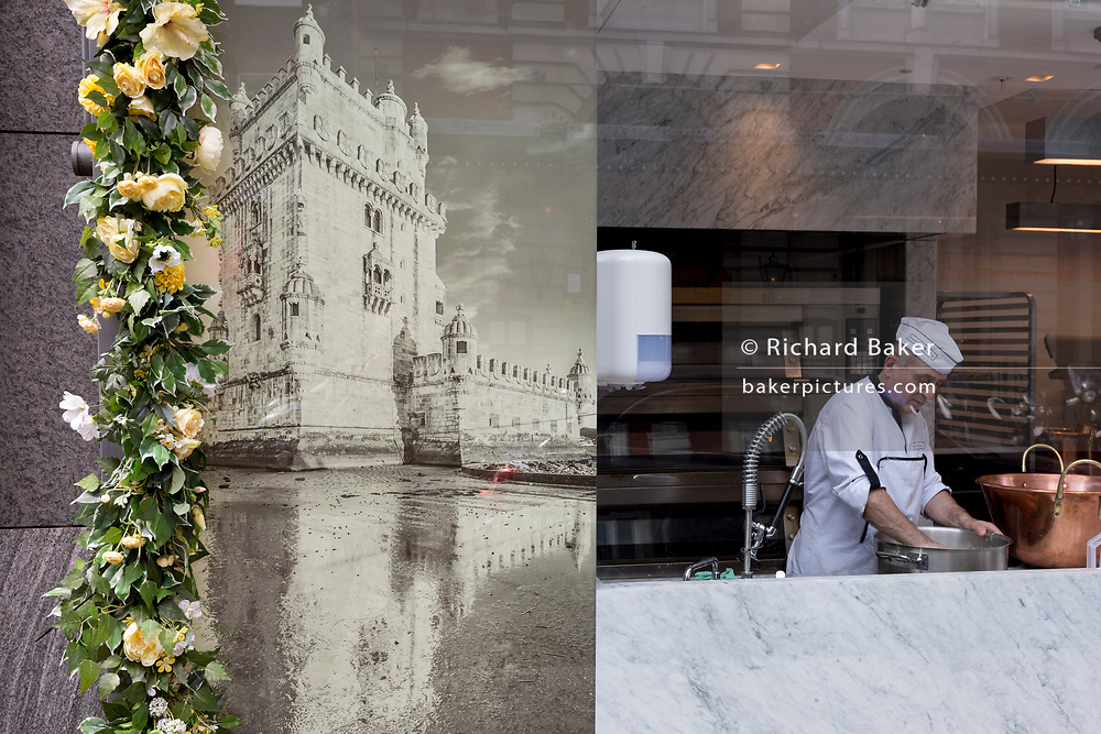 An image of the Belem Tower in Lisbon and the window of a cake and pastry business in which a baker washes a heavy pan , on 22nd May 2019, in London, England