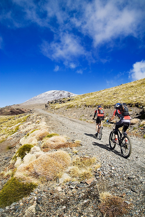Two mountain bikers ride the trail to Mulhacen, visible dusted in snow in the distance, Sierra Nevada National Park, Andalusia, Spain. Mulhacen is the highest mountain in continental Spain.