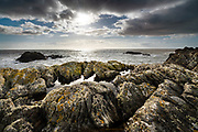 I love it when after leaving home which is covered by cold grey sky, I find myself half an hour later standing on a cliff top with sunshine warming my face. As the afternoon sunshine dropped lower in the sky, it broke below blankets of heavy cloud and blasted the sea and cliffs with intense light, illuminating rock pools and sharpening blades of rock. Getting to the sea has always meant escape to me, a chance of adventure and journey. Looking out towards a sunlit horizon means so much to me, especially hope.