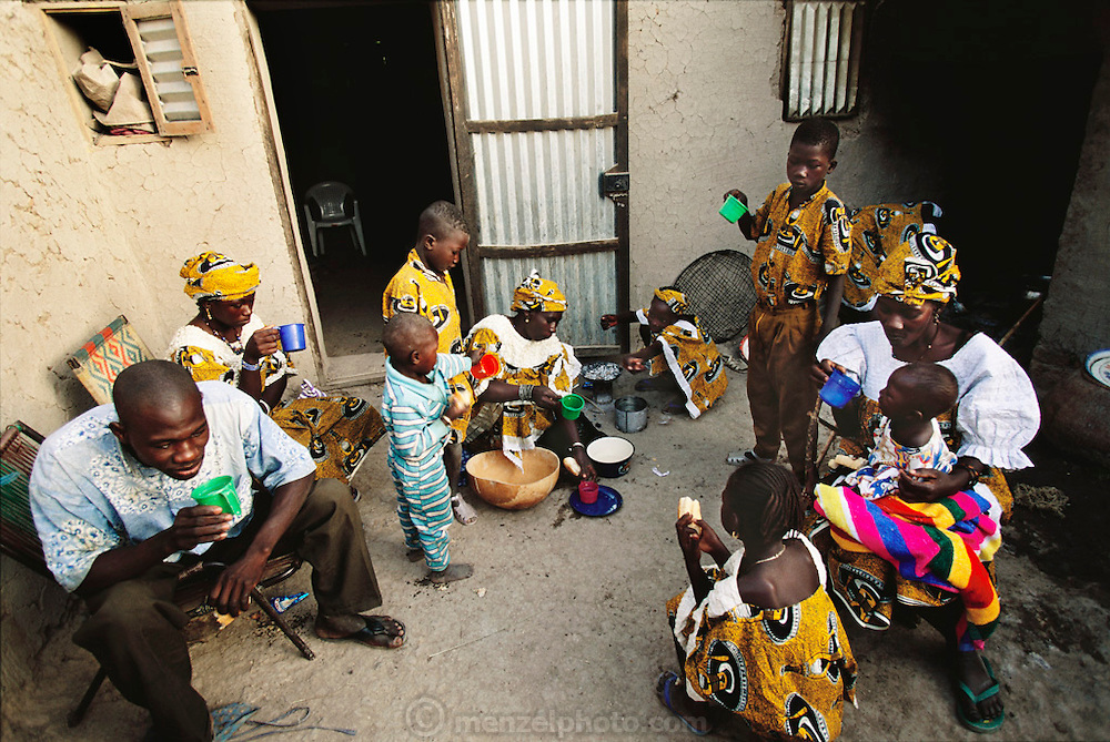 Kouakourou Village, Mali. Pama Kondo's second eldest daughter, Pai, 18, at right with blue cup, will be married today to her first cousin, Baba Nientao (at left holding green cup), who has come back from the Ivory Coast where he has lived with his family since he was 12 years old. The arranged marriage was revealed to Pai this morning by her father, as is the custom, and she is quiet as part of the ritualized mourning for her lost youth. Her mother, Pama, center, serves the children a grain drink and her mother's co-wife Fatoumata Toure is at right.