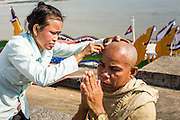 """03 FEBRUARY 2013 - PHNOM PENH, CAMBODIA: Cambodians have their heads shaved to honor former King Norodom Sihanouk, who ruled Cambodia from independence in 1953 until he was overthrown by a military coup in 1970. In Cambodian culture, widows and children shave their heads to honor their husband or father. King Sihanouk, whose final title was """"King-Father"""" was viewed as the father of his country because he secured Cambodia's independence from the French. The only music being played publicly is classical Khmer music. Sihanouk died in Beijing, China, in October 2012 and will be cremated during a state funeral royal ceremony on Monday, Feb. 4.     PHOTO BY JACK KURTZ"""