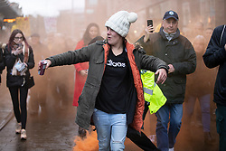 © Licensed to London News Pictures. 12/12/2020. Manchester, UK. A woman passes through a smoke bomb as crowd marches through Manchester with with signs for North Unites protest in Piccadilly Gardens, Manchester. Piers Corbyn is expected to make a speech later. Photo credit: Kerry Elsworth/LNP