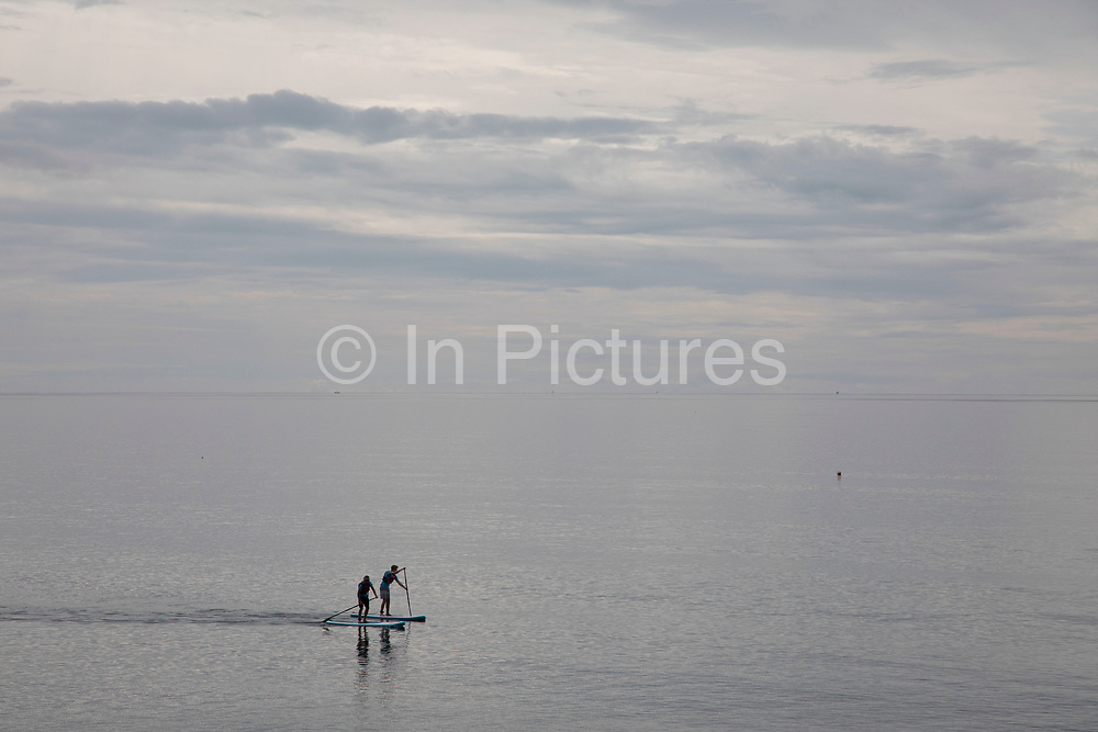 Coastal view of two people paddle boarding on the sea in Seaton in Devon, England, United Kingdom. Seaton is a small seaside town in East Devon on the south coast of England.