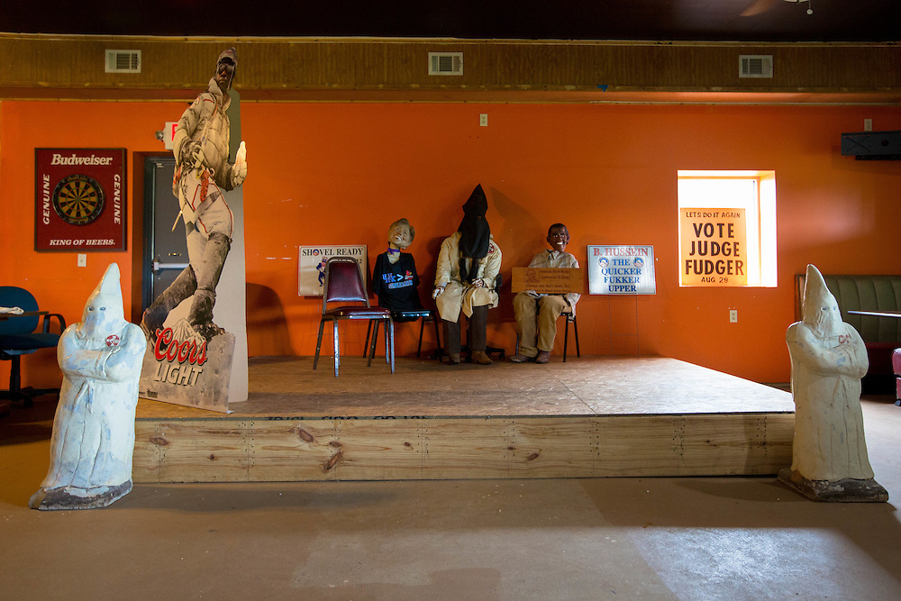 """The back room of Georgia Peach Oyster Bar in Paulding County, Ga., features a KKK member sitting between caricatures of President Obama (back right) and Hillary Clinton. Obama's caricature is holding a sign that reads """"America's Porch Monkey. Commander and Chimp!"""" The bar and restaurant is owned by Patrick Lanzo, who says he is on the FBI's Terrorist Watchlist for many of the controversial things he has done, including placing signs out front of his business that read """"Obama. A vision of a dream. James Earl Ray."""" This photograph was taken on Thursday, July 2, 2015. Shot for a story about changes occurring in the South following a heightened national awareness and sensitivity concerning the Confederate battle flag. Photo by Kevin Liles for The New York Times"""