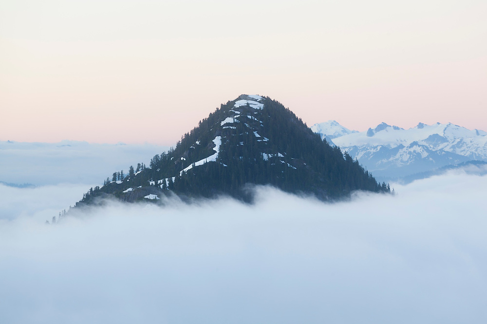 Oakes Peak rises above the low clouds filling Bacon Creek drainage, Mount Baker-Snoqualmie National Forest, Washington. Snowking Mountain is visible in the distance.