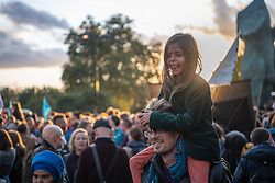 © Licensed to London News Pictures. 06/10/2019. London, UK. Siahni (6 Years) sits on Rodney, her father's shoulders. Extinction Rebellion (XR) activists gather in Marble Arch ahead of a week of planned actions across the capital. A ceremony was performed lighting a beacon and torches. Photo credit: Guilhem Baker/LNP