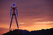 The 50-foot tall Burning Man, outlined in neon, at dawn. Burning Man is a performance art festival known for art, drugs and sex. It takes place annually in the Black Rock Desert near Gerlach, Nevada, USA..