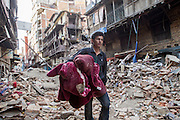 KATHMANDU, NEPAL - APRIL 26: (CHINA OUT)<br /> <br /> A man holding quilt passes by the ruins on April 26, 2105 in Kathmandu, Nepal. A 8.1-magnitude earthquake struck Nepal on Saturday and the earthquake felt in southeast China\'s Tibet Autonomous Region which brought some houses into collapse. While another 7.1-magnitude earthquake hit the county again the following day afternoon. Chinese government sent out Sichuan Rescue Team, the only one national emergency medical rescue team who could settle camps above an altitude of 3500 meters, to Nepal to support local rescue work and international assistance were also sent to the disaster areas. The earthquake had caused at least 3218 people to death and parts of Chinese visitors were detained in Nepal by Monday morning. <br /> ©Exclusivepix Media
