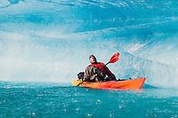 A man on kayak drinks water from a melting iceberg on Bear Lake in Kenai Fjords National Park, Alaska.