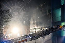 © Licensed to London News Pictures . 01/01/2018. Liverpool, UK. Fire hose jets are sprayed in to the car park (pictured with charred metal facia boards in the centre of the picture , with Liverpool's iconic Freijwheel  ferris wheel behind) . Scene at the Liverpool Echo Arena car park where firefighters are working to extinguish a fire that started late on New Year's Eve and that destroyed all 1,400 cars parked in the multi-story car park. The Liverpool International Horse Show taking place at the Arena was abandoned and people and horses evacuated as dozens of fire crew worked to control the blaze . Photo credit: Joel Goodman/LNP