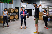 """22 JULY 2020 - AMES, IOWA: THERESA GREENFIELD (center) and ELLIOT THOMPSON, owner of Alluvial Brewing, talk about the needs of small businesses during a visit by Greenfield to Alluvial Brewing in Ames, IA. Greenfield, a Democrat, is running for the US Senate against incumbent Republican Senator Joni Ernst. Recent polls have Greenfield slightly ahead of or statistically tied with Ernst, who is closely allied with President Donald Trump. Although Greenfield is not doing much in person campaigning with big events, she is meeting with business people across the state of Iowa to promote her """"Small Towns, Bigger Paychecks"""" economic program.       PHOTO BY JACK KURTZ"""