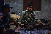 A member of the Free Syrian Army (FSA) awaits sat at an outpost next to his rifle as he expects a shift change at the FSA military checkpoint in Marea on Monday, June 25, 2012. (Photo by Vudi Xhymshiti)