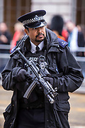 An armed police officer keeps watch as the coffin of baroness thatcher passes along Fleet Street on route to St. Paul's cathedral where her funeral took place. 17th April 2013. London, United Kingdom.